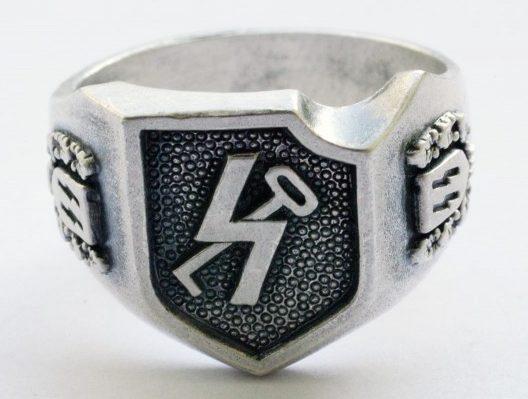 Перстень с рельефным изображением символа 12-й танковoй дивизии СС «Гитлерюгенд» выполнен из серебра 835-й пробы с применением чернения поля щитка. По сторонам щитка - руны СС в орнаменте из дубовых листьев.