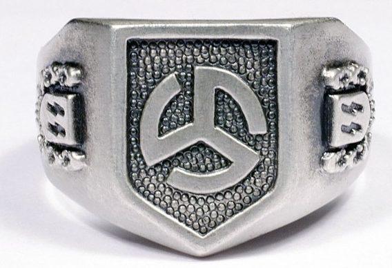 На щитке перстня рельефное изображение эмблемы 27-oй добровольческой пехотной дивизии СС «Лангемарк» (фламандская № 1). По сторонам щитка - руны СС в орнаменте из дубовых листьев. Кольцо изготовлено из серебра 835-ой пробы с применением чернения.