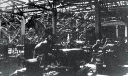 Работа на уцелевших станках в поврежденном во время налетов инструментальном цехе. На заднем плане видны обрушившиеся металлоконструкции перекрытий.