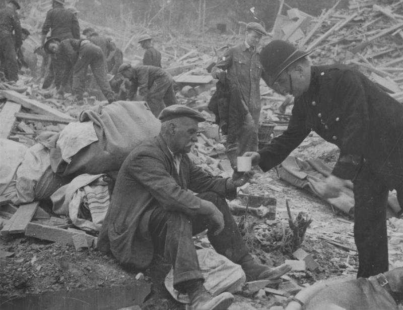 Полицейский дает чашку чая мужчине, оставшемуся без крова после падения на его дом немецкой ракеты ФАУ-1. 1944 г.