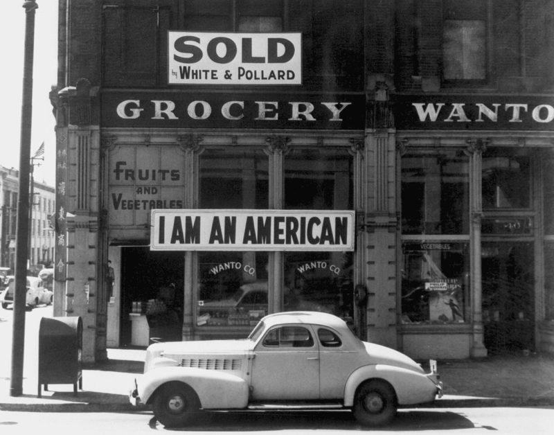 «Я американец». Японец вывесил этот плакат на следующий день после атаки на Пёрл-Харбор. Этот снимок был сделан прямо перед тем, как этого человека увезли в лагерь. Март 1942 г.