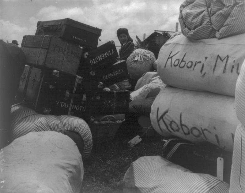Японка ищет свои вещи на сборном пункте в Салинасе (Калифорния). На всех чемоданах и баулах видны фамилии их владельцев. Март 1942 г.