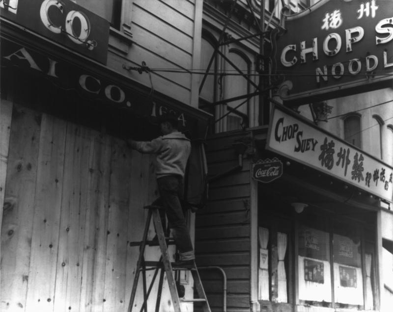 Японец забивает двери своего магазина перед отправкой в лагерь. Апрель 1942 г.