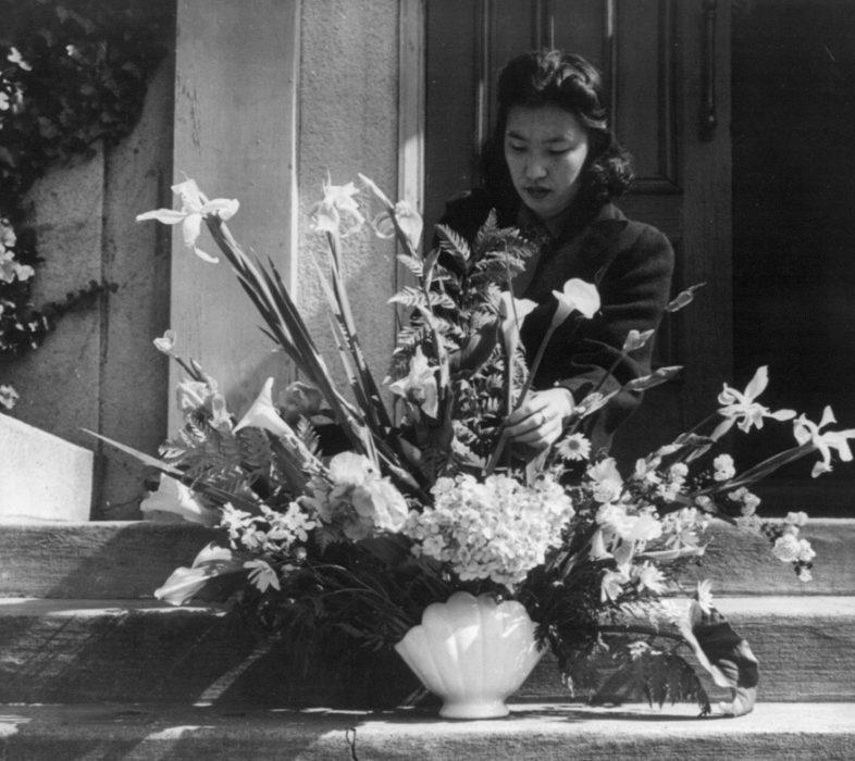 Японка с букетом цветом у порога своего дома перед отправкой в лагерь. Апрель 1942 г.