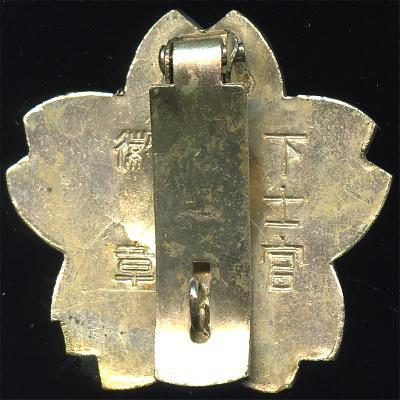Аверс и реверс «Знака владения мечом/штыком» для унтер-офицеров. Знак выполнен из серебра. Аверс знака позолочен, ободок знака по периметру – имеет серебристый цвет.