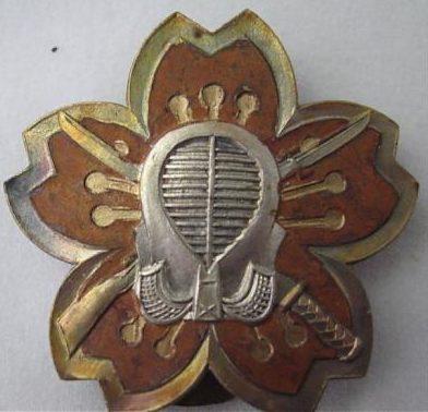 Аверс и реверс знака 1-го класса владения мечом/штыком для рядовых. Знак выполнен из бронзы. Защитная маска на аверсе знака выполнена серебристым цветом, ободок знака по периметру - золотистый. Знак являлся старшим знаком по отношению к знаку 2-го класса.