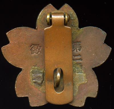 Аверс и реверс знака 2-го класса владения мечом/штыком для рядовых. Знак выполнен из бронзы. Ободок знака по периметру и винтовка с мечом - золотистые. Знак являлся младшим знаком по отношению к знаку 2-го класса.