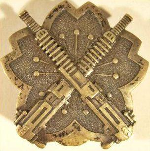 Аверс и реверс латунного знака «За стрельбу из тяжелых пулемётов» образца 1939 г.