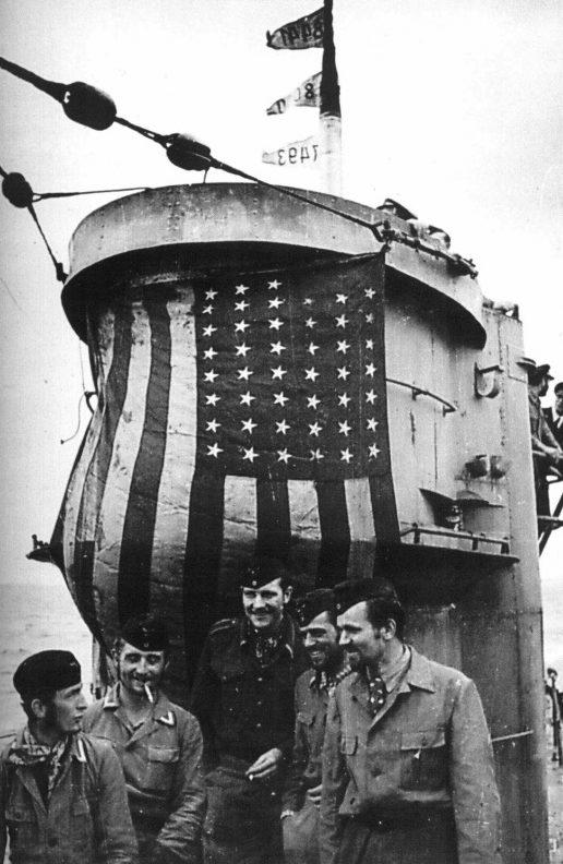 Подводники у захваченного флага с американского судна, растянутого на рубке. 1942 г.