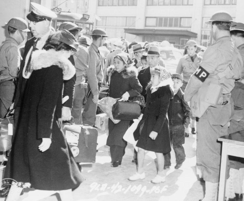 Японская семья на вокзале Сан-Франциско в конвое военной полиции во время депортации в лагерь. Апрель 1942 г.
