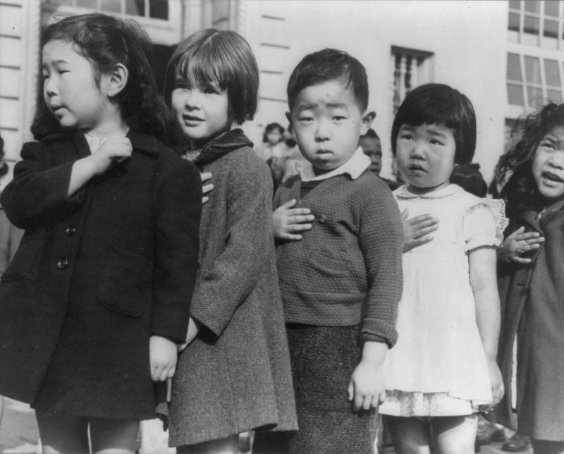 Японские и американские дети на церемонии подъема флага в школе Вэйлл в Сан-Франциско. Большинство из японских детей на этих фотографиях были депортированы в лагеря для интернированных вскоре после того, как эти фото были сделаны. Апрель 1942 г.
