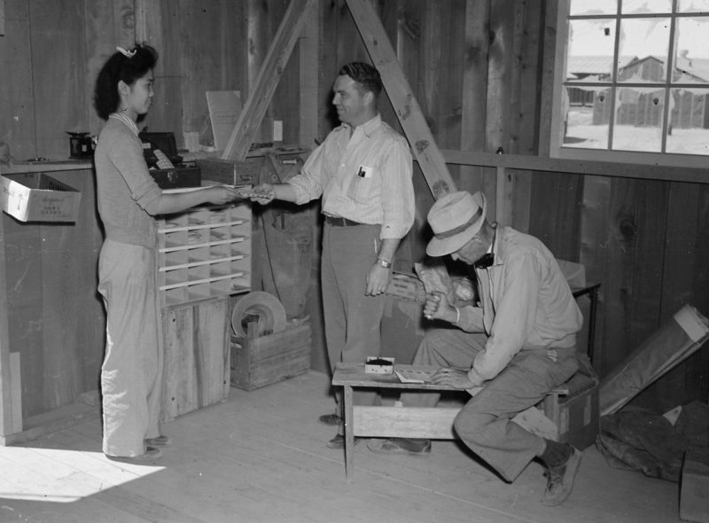 Первый клиент пользуется почтовым отделением в лагере «Постон». 1943 г.