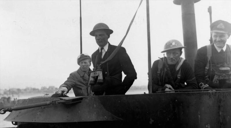 Британские моряки и командир капитулировавшей подлодки «U-249» Уве Кок в порту Лондондерри. Май 1945 г.