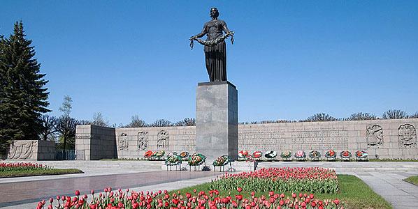 Памятник и стена с барельефами.