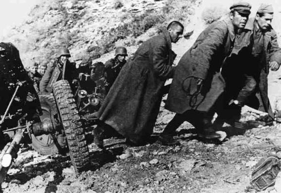 Помощники из красноармейцев тянут орудие. 1941 г.