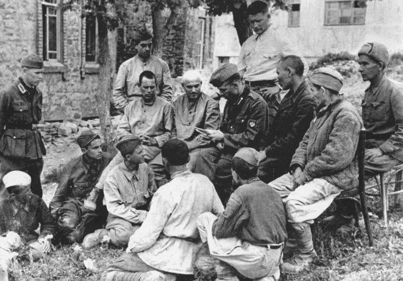 Пропагандист РОА читает воззвание генерала Власова советским военнопленным. Май 1943 г.