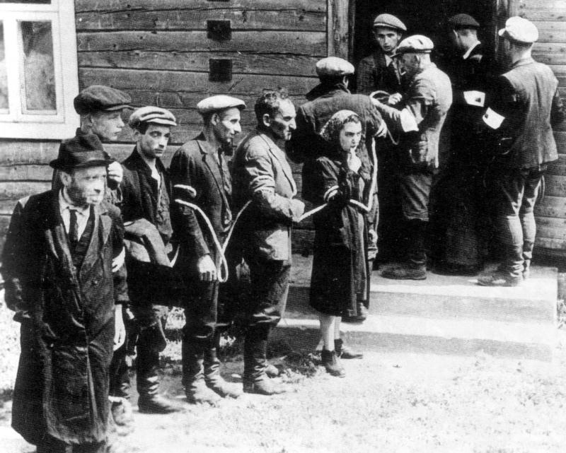 Связанные евреи, охраняемые литовской вспомогательной охраной. Июль 1941 г.