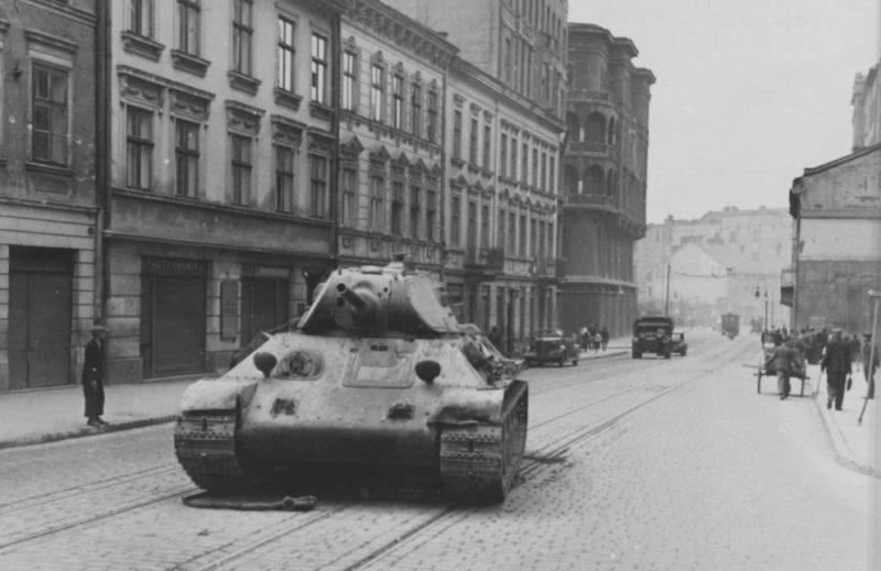 Поломанный танк Т-34 на улице города. Июнь 1941 г.