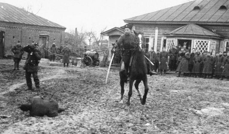 Приблизительно так воевали казачки. Казак-полицай на потеху венгерским оккупантам рубит шашкой пленных советских партизан. Украина, ноябрь 1941 г.