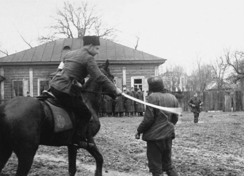 Казак-полицай на потеху венгерским оккупантам рубит шашкой пленных партизан. Ноябрь 1941 г.
