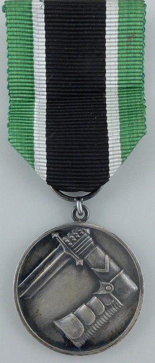Аверс и реверс серебряной медали Шюцкора «За заслуги».
