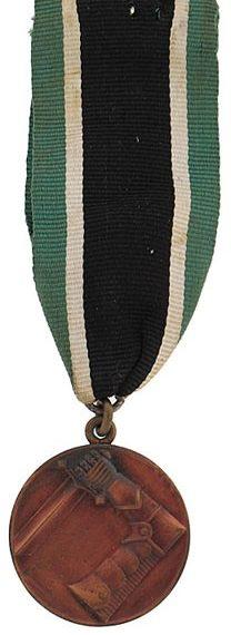 Аверс и реверс бронзовой медали Шюцкора «За заслуги».