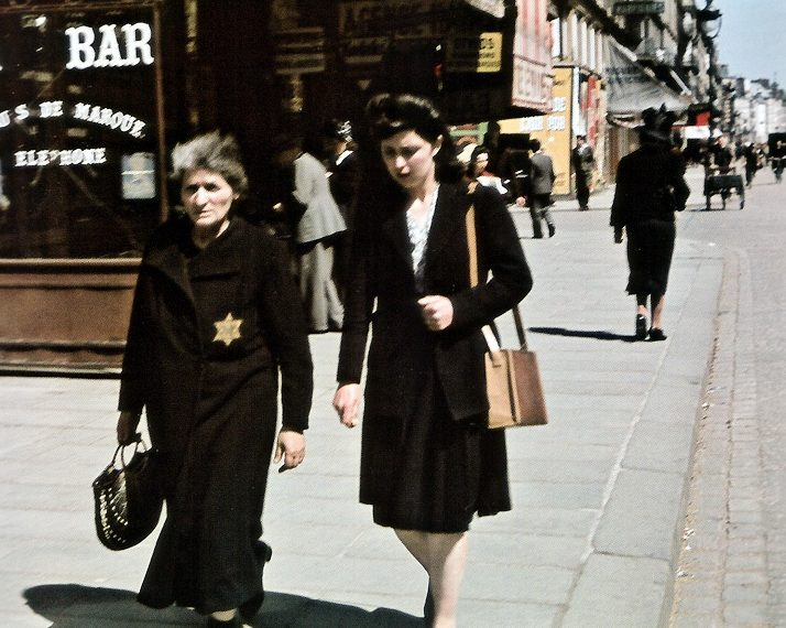 Пожилая еврейка с нашивкой на груди на улице. Осень 1940 г.