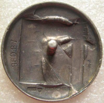 Аверс и реверс серебряного знака «За заслуги» Шюцкора 1-го класса. Изображение руки в доспехе с мечем – позолочено.