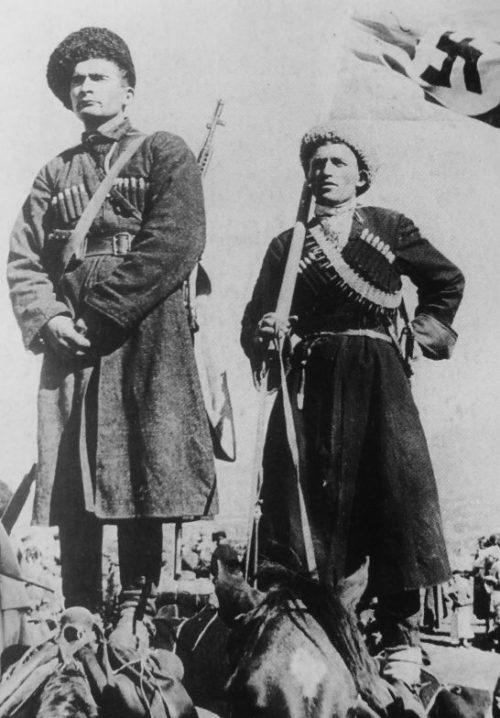 Казаки-хиви позируют с флагом, стоя на спинах лошадей. 1943 г.