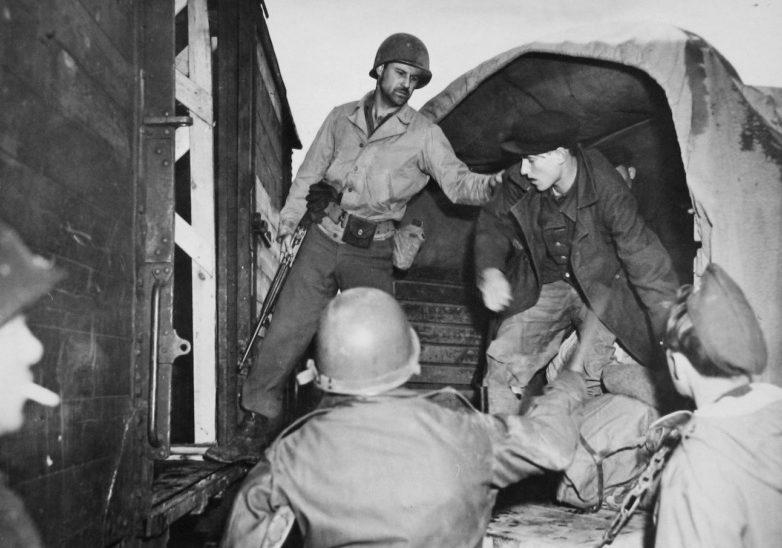 Пленный хиви оказывает сопротивление конвоирам 66-го пехотного полка США, отказываясь переходить из грузовика в железнодорожный вагон, предназначенный для передачи Советской стороне в районе города Хоф. Германия, 1945 г.