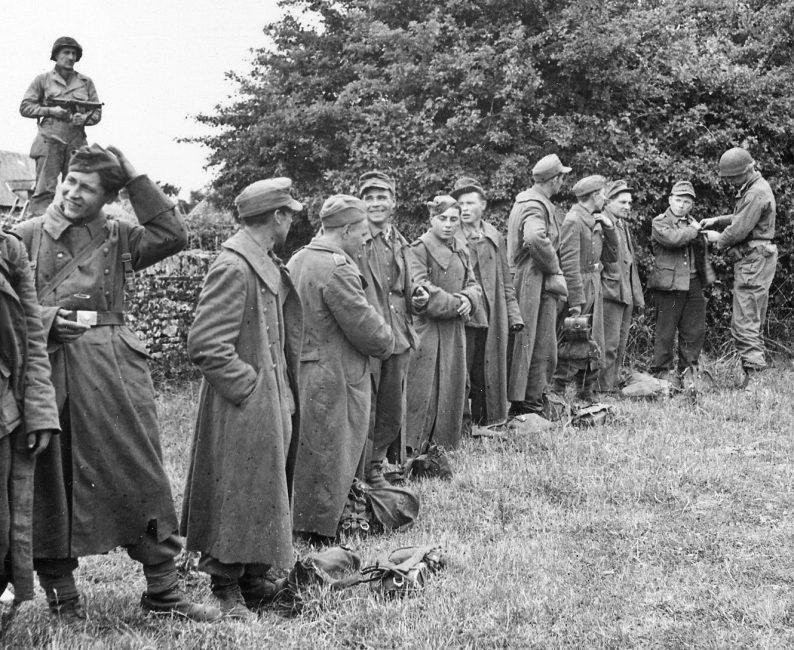 Солдаты 1-й армии США проводят обыск пленных хиви. Июль 1945 г.