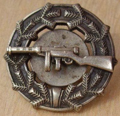 Аверс и реверс знака «За стрельбу из пистолета-пулемета» образца 1933 г.