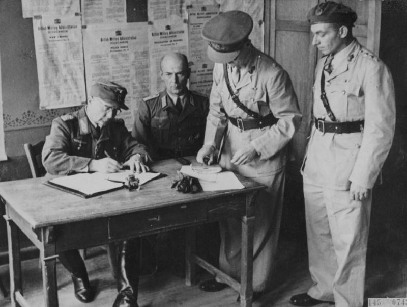 Командующий немецкими войсками в Додеканесе генерал-майор Отто Вагенер подписывает безоговорочную капитуляцию в присутствии британских офицеров. Май 1945 г.