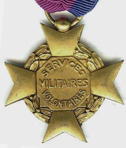Аверс и реверс золотого креста «За добровольную воинскую службу» 1-й степени I типа. На орденской ленте размещалась розетка в цветах ленты.