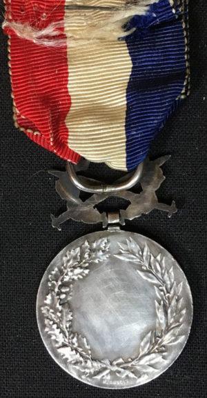 Аверс и реверс серебряной Почетной медали Министерства иностранных дел с мечами.