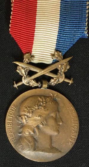 Аверс и реверс бронзовой Почетной медали Министерства иностранных дел с мечами.