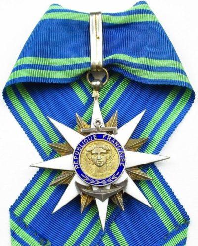 Золотой знак Командора ордена Морских заслуг на шейной ленте.
