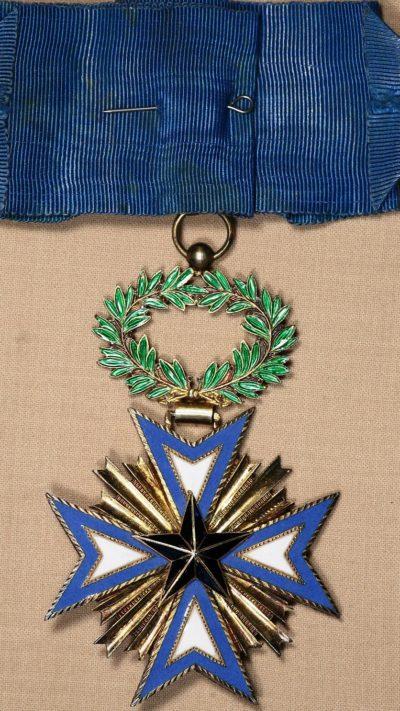 Аверс и реверс золотого знака Командора ордена Чёрной звезды на шейной ленте.