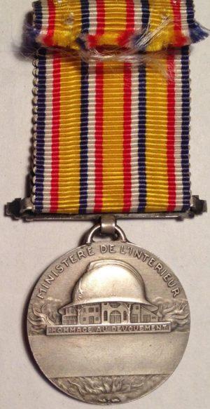 Аверс и реверс серебряной Почетной медали пожарных.