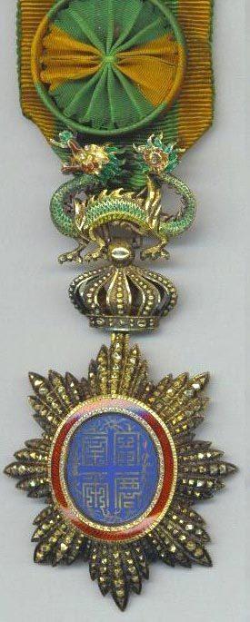 Аверс и реверс знака офицера ордена Дракона Аннамы на орденской ленте с розеткой.