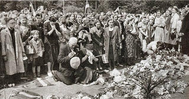 Местные жители возлагают цветы к монументу Свободы после захвата немцами города. Июль 1941 г.