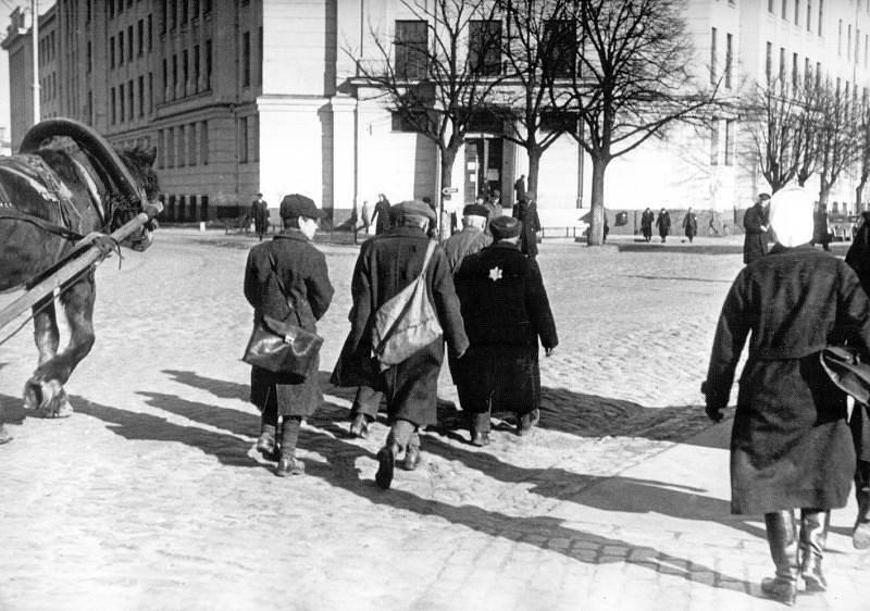 Евреи возвращаются с принудительных работ в гетто, по проезжей части, поскольку ходить по тротуарам им запрещено. Октябрь 1941 г.