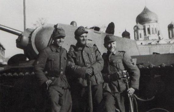 Оккупанты позируют на фоне подбитого советского танка КВ на Базарной (Соборной) площади. Июль 1942 г.