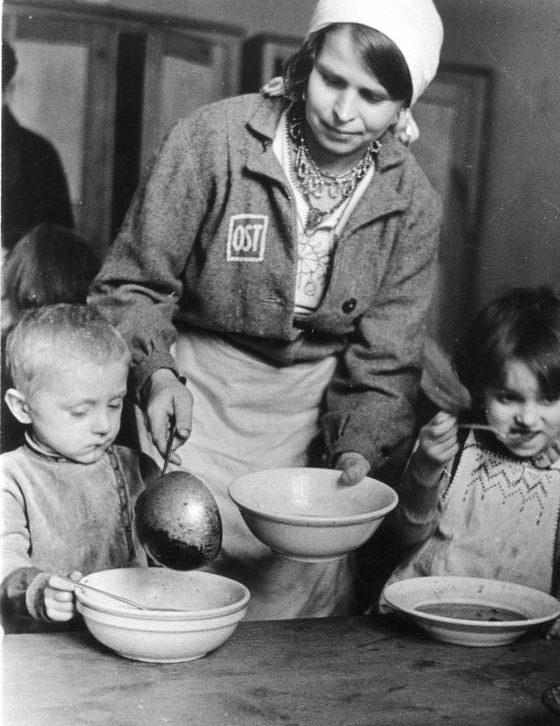 Раздача пищи в детских яслях трудового лагеря. Фотография немецкой пропаганды. Февраль, 1944 г.