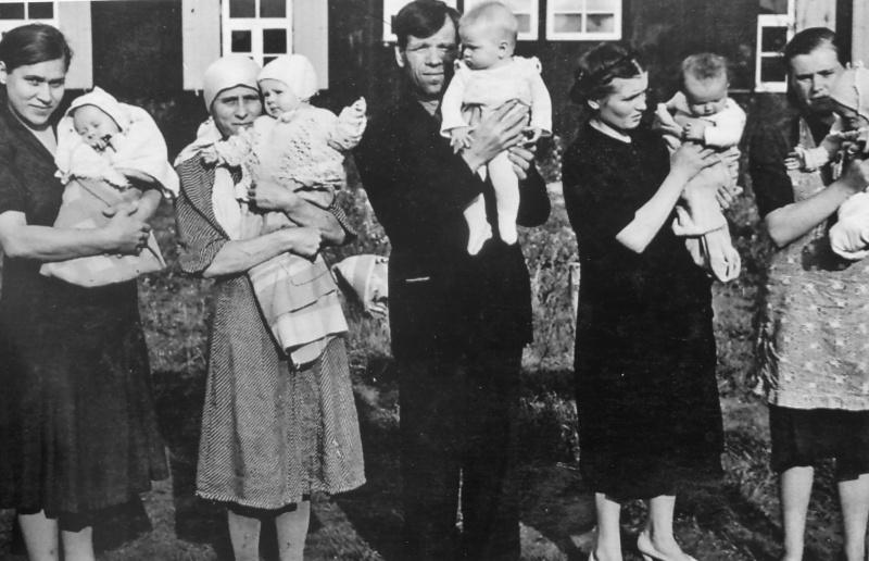 Родители с детьми у барака в лагере для подневольных советских рабочих при автозаводе «Форд» в Кельне. 1944 г.