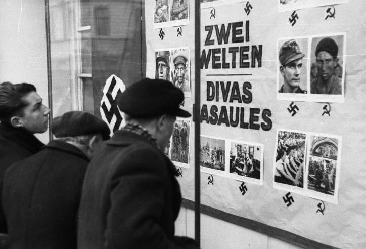Горожане изучают немецкую агитпродукцию. 1943 г.