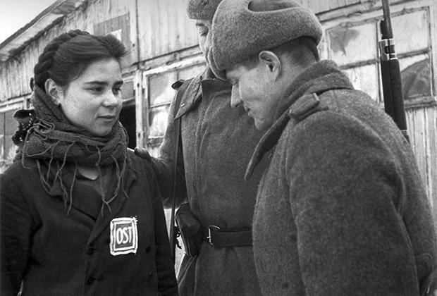 Красноармейцы беседуют с советской девушкой-остарбайтером, работавшей на немецком заводе «Юнкерс» в городе Познани. Польша, февраль 1945 г.