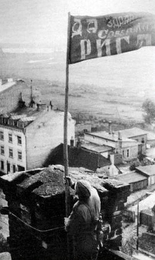 Водружение знамени на одном из зданий освобожденного города. Октябрь 1944 г.