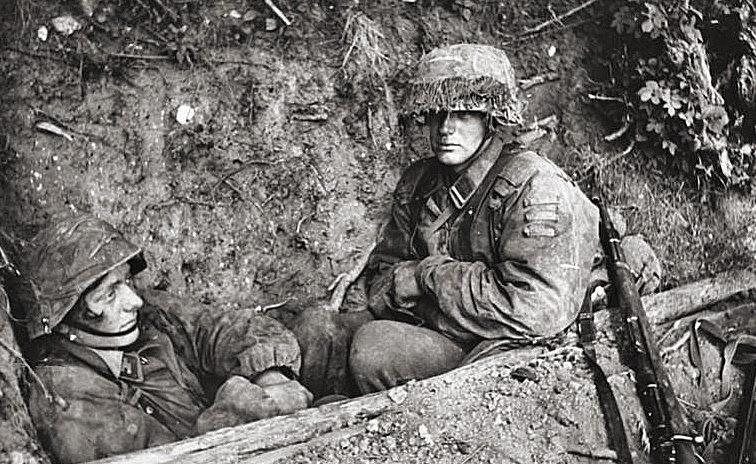 Немецкие пехотинцы в перерыве между боями. Нормандия. 1944 г.