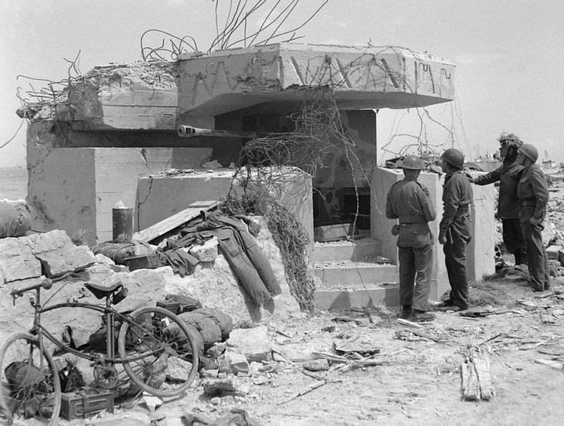 Союзники у разрушенного артиллерийского ДОТа с 50-мм орудием. Золотой пляж. Июнь 1944 г.